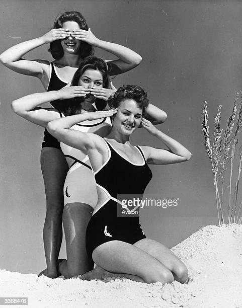 Swimwear models posing as the three wise monkeys hear no evil speak no evil and see no evil