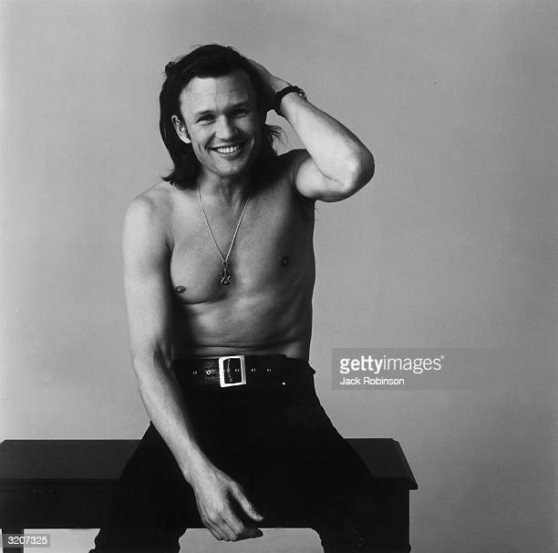 Portrait of American country singer and songwriter Kris Kristofferson sitting on a bench and running his hand through his hair He is barechested