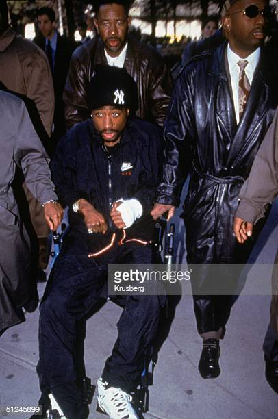 1st December 1994 American rapper and actor Tupac Shakur is helped out of court in a wheechair the day after his shooting