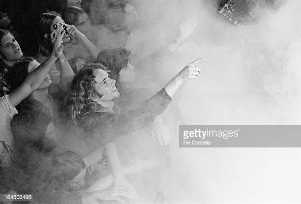 Audience members and fans of the rock group Deep Purple watch the band perform through dry ice and smoke on their North American tour in December 1974