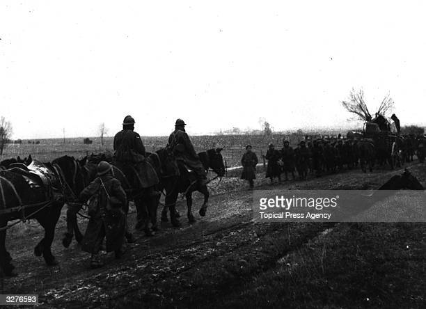A French infantry column pass supply carts on their way back from the lines