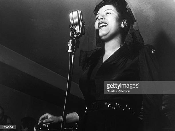 American jazz singer Billie Holiday sings in front of a microphone at a Sunday afternoon jam session at Ryan's on 52nd Street New York City