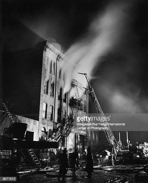 Firemen fight to put out the flames of a burning mattress factory on Willoughby Street Brooklyn New York Photo by Weegee/International Center of...