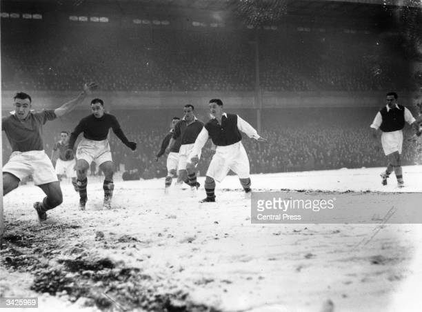 Manchester United's goalkeeper out of position and stranded looks on as one of his defenders attempts in vain to stop the ball from going over snow...