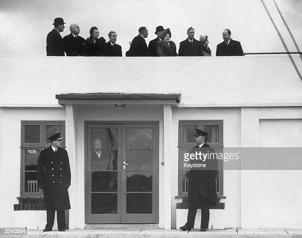 King George VI and Queen Elizabeth watching Princess Elizabeth's plane flying to Kenya from a rooftop at London Airport Prime Minister Winston...