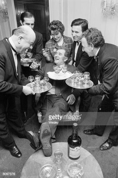 Miner Alan Wilkinson is served samples of 'Dry Sack' sherry at the Dorchester Hotel in London watched by his wife He is the winner of a competition...