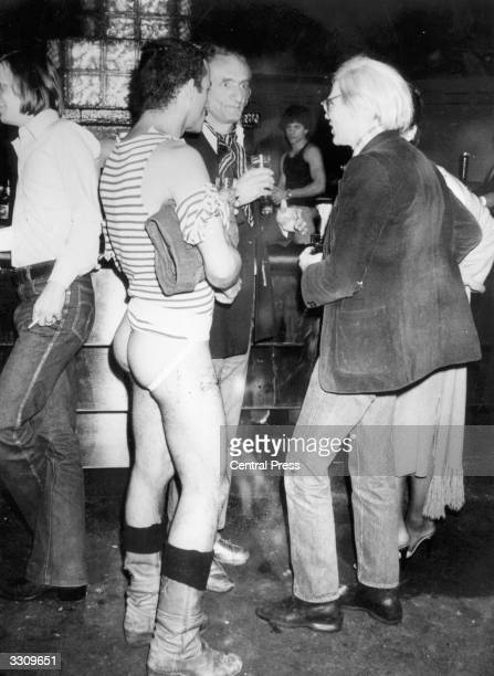 Pop artist Andy Warhol stands next to a man wearing a jockstrap at New York's Studio 54 disco