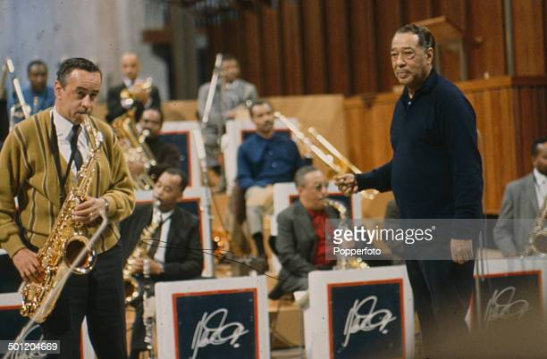 American composer and pianist Duke Ellington pictured with tenor sax player Paul Gonsalves and the Duke Ellington Orchestra in rehearsal at Coventry...