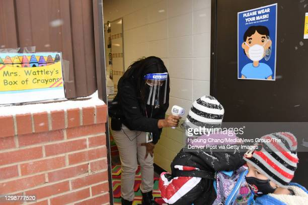 1st grade teacher Raven Wattley, left, checks body temperature of students by the entrance of the class room at Rose Hill Elementary school in...