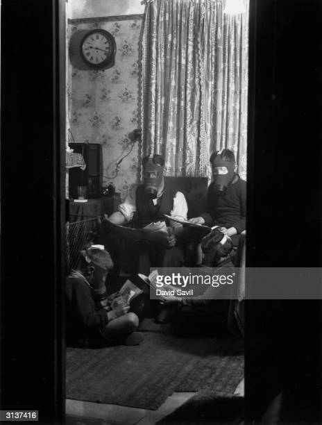Father instructs his sons in the proper way to wear a gas mask, at their London home.