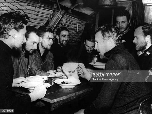 Officers and crew of a German submarine enjoy a meal in the cramped quarters aboard their vessel
