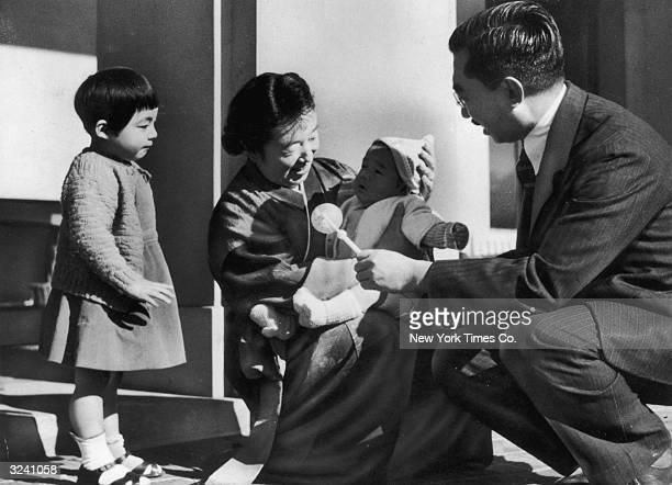 Japanese Emperor Hirohito and his wife Nagaka play with their grandchildren Yasuko and Hideatsu children of their eldest daughter Princess Shigeko...