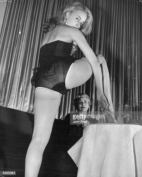 20 year old South African beauty Kathy Keeton works as a striptease artist at London's 'Embassy Club' Seated at the table sewing Gstrings for her...