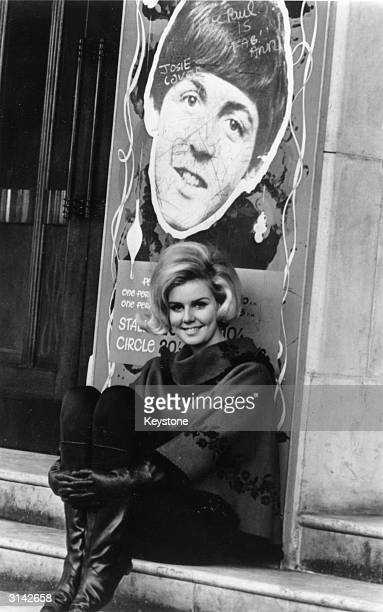Beatles fan 20year old Miss Finland of 1962 Kaarina Leskinen sits in a doorway underneath a poster displaying the face of Paul McCartney