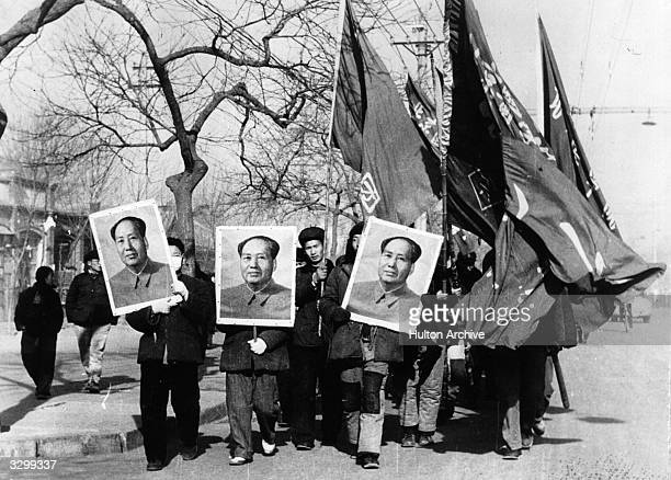 Members of the Red Guards carry large portraits of Mao Tse Tung as they parade through the streets of Peking .