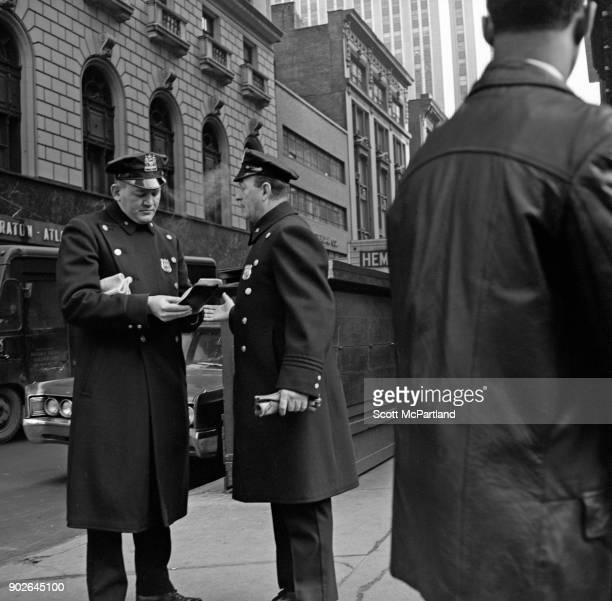 Two NYPD police officers in full uniform have a discussion on Seventh avenue in Times Square New York