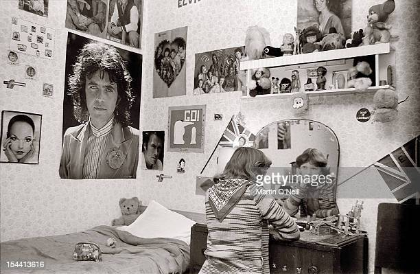 A young girl sits in her bedroom looking at her reflection in a mirror with posters of pop stars including David Essex on the bedroom walls in 1977...