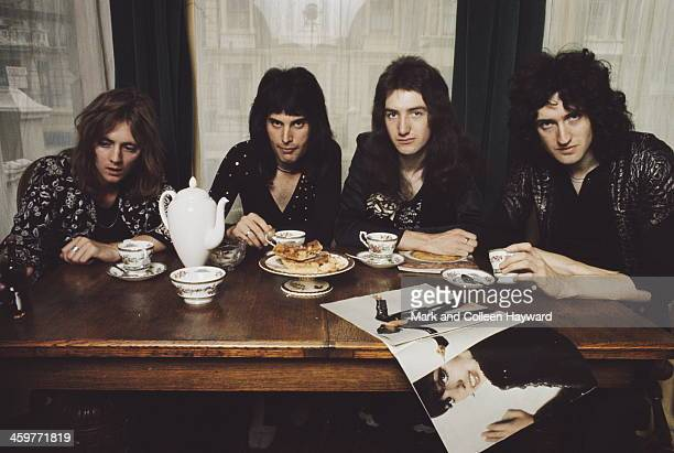 English rock group Queen posed at a dining table in lead singer Freddie Mercury's flat Holland Road West Kensington London in early 1974 Left to...