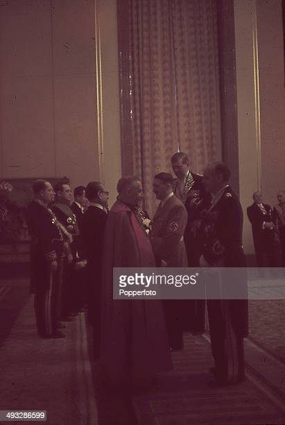 German Chancellor Adolf Hitler and Foreign Minister Joachim von Ribbentrop in diplomatic dress greet guests including papal nuncio Cesare Orsenigo at...