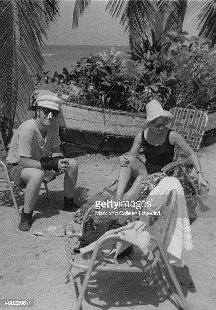 John Lennon from The Beatles relaxes in the sun with his wife Cynthia Lennon on holiday in Port Of Spain Trinidad in January 1966