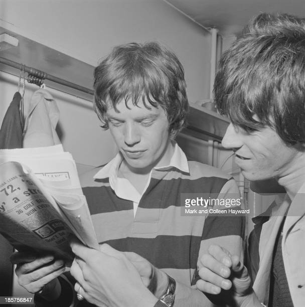 Mick Jagger and Keith Richards from The Rolling Stones read a newspaper backstage on tour in Scotland in early 1964