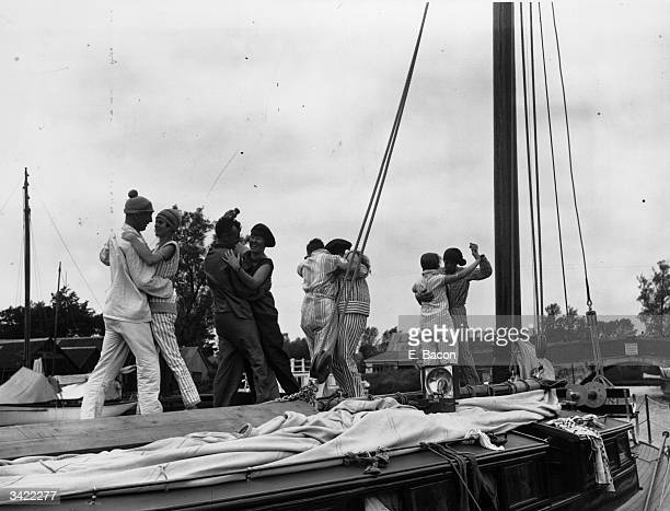 Collection of couples wearing their pyjamas to dance on deck during their holiday on the Norfolk Broads.