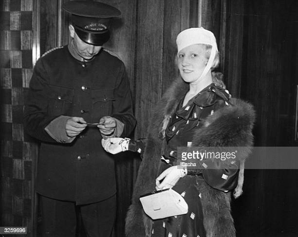 A woman shows her ticket to a doorman for the first night of the play 'Fanfare' at the Prince Edward Theatre in London