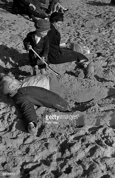 Dad being buried on Blackpool Beach. Original Publication: Picture Post - 167 - So This Is Blackpool - pub. 1939