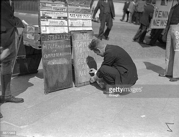 Because of the shortage of paper a newsvendor writes on a blackboard One headed 'Standard' reads Hitler and Ciano in complete agreement'