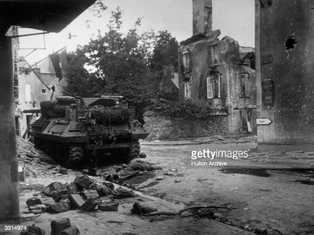 A dead American soldier lies in front of a US Tank Destroyer at the entrance to St Lo