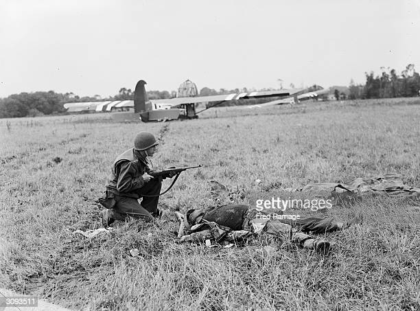 An American soldier crouching by the body of a dead German soldier with US Waco troop carrying gliders on the field behind him in Normandy