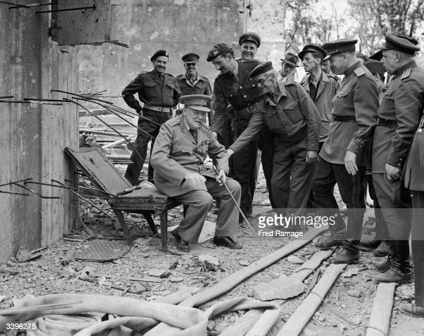 During his visit to a conquered Berlin British Prime Minister Winston Churchill takes a rest on Hitler's chair outside the Berlin Bunker