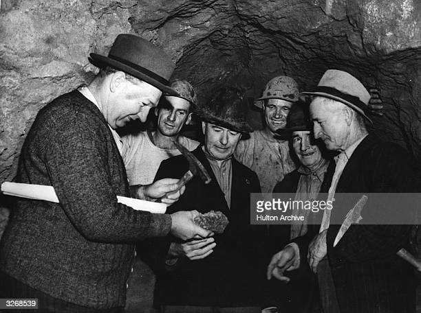 Politicians and prospectors examining a sample of uranium ore in a mine north of Adelaide Australia