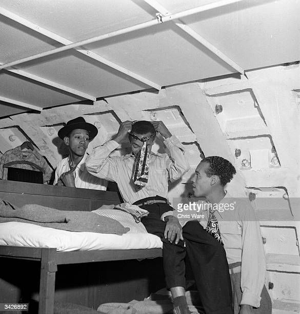 In their small bedroom in the Clapham Shelter Kenneth Murray Eric Dryndale and Aston Robinson three men from Kingston Jamaica get ready to explore...