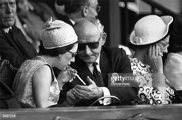 Wearing a matching dress and hat Princess Margaret sister of Queen Elizabeth II accepts a light for her cigarette from her companion in the royal box...