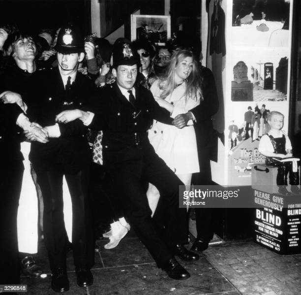 Police hold back some of the 5000 fans who have arrived to see the pop group The Beatles at the premiere of their latest film 'Yellow Submarine' at...