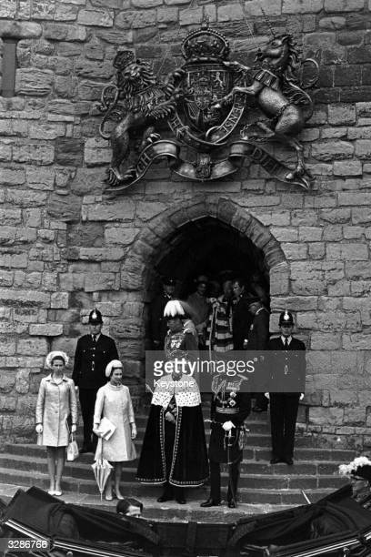Charles Prince of Wales with Queen Elizabeth II Princess Anne and Prince Philip Duke of Edinburgh at the entrance to steps of Caernarfon Castle Wales...