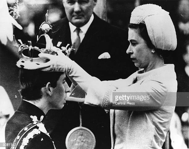 The Queen placing the coronet of The Prince of Wales on Charles, Prince of Wales' head during his investiture ceremony whilst an official holds the...