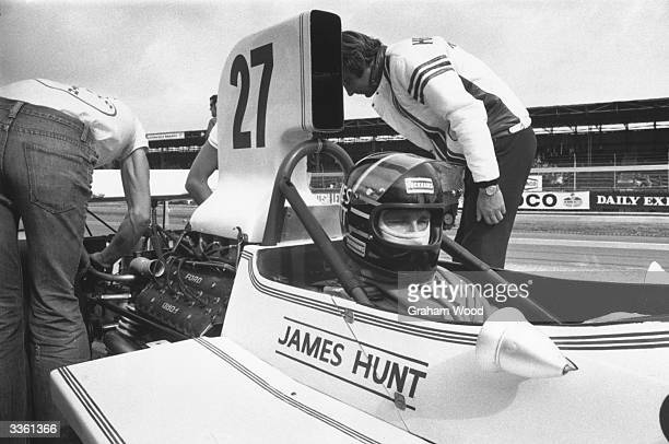 British racing driver James Hunt sitting in his Hesketh F1 racing car during the British Grand Prix at Silverstone