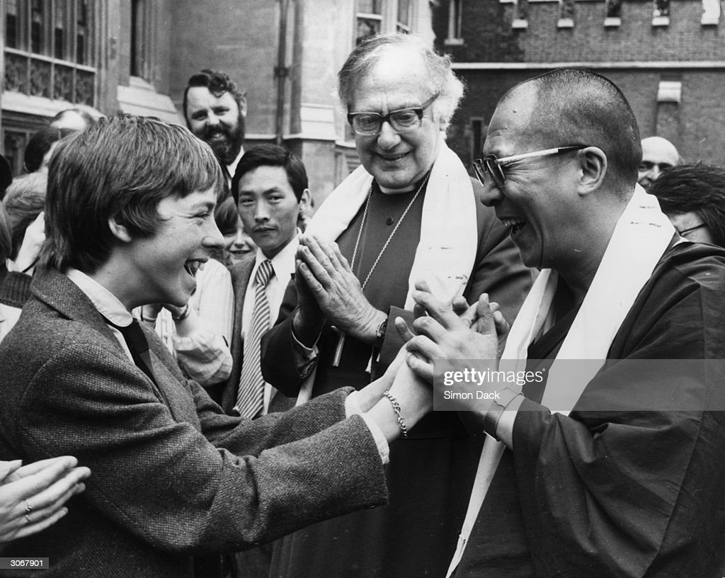 The Dalai Lama greets 15 year old Stephen Ross from the Kelvin School, Belfast who is on a visit to Lambeth Palace, London. They are watched by Dr Robert Runcie, the Archbishop of Canterbury. In the background is bearded Terry Waite, 'special envoy' to the Archbishop.
