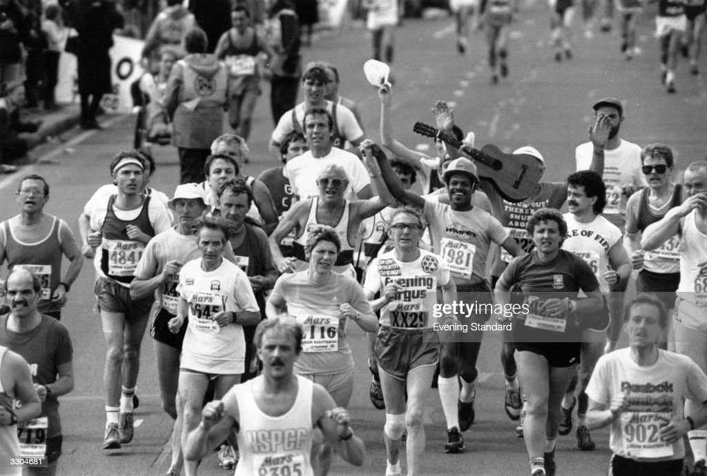 A group of London Marathon runners, including radio and television broadcaster Jimmy Savile (centre) and a man with a guitar.