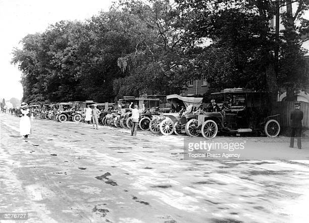 Motor cars lined up in the road as crowds arrive at Ascot.