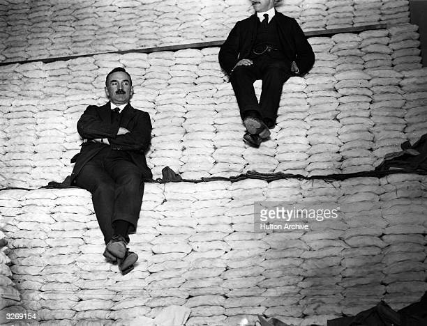 Two men sitting on a huge pile of coins which after being weighed and packed have been stacked into neat rows at the Royal Mint.