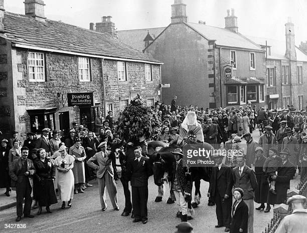 Garland day at Castleton Derbyshire A veiled woman on a horse is led through the streets by a man in an embroidered coat Another horse carries a huge...