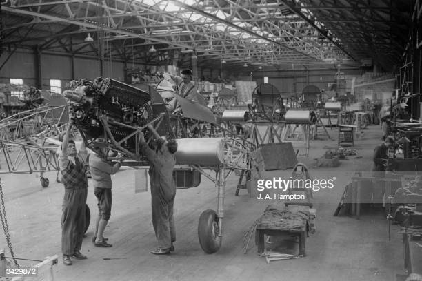 Pilot's decking and engine being installed at the factory of Hawker Aircraft Ltd during the construction of Hawker Hurricanes part of the RAF...
