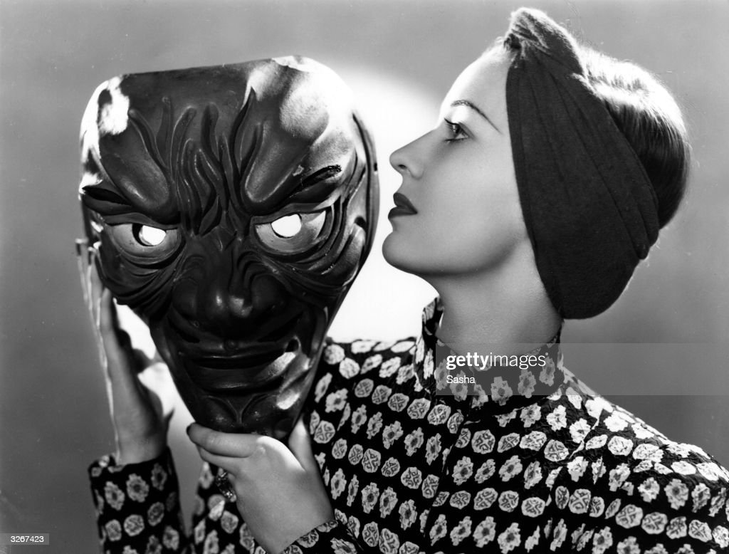 Valerie Hobson (1917 - ) the British leading lady posing in profile and holding a large grotesque face mask in her hands.