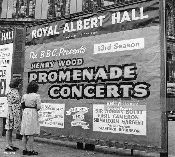 Two women studying a poster advertising the 1947 Proms season at the Royal Albert Hall including concerts conducted by Sir Adrian Boult Basil Cameron...