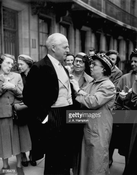 Bystander Miss Lucy Blake fixes the buttohole of Lord Fermoy at the wedding of his daughter the Hon Frances Roche to Viscount Althorp at Westminster...