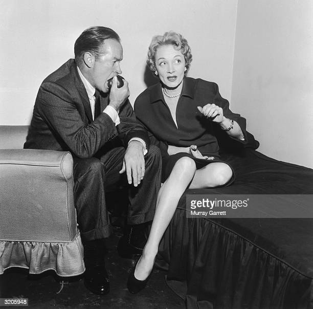 American comedian and actor Bob Hope bites into an apple as he sits with German-born actor Marlene Dietrich backstage at the Bob Hope radio show, Los...