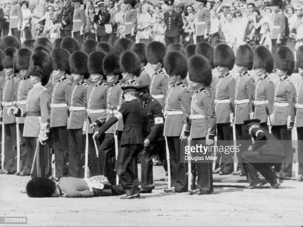 First aid attendants helping a Guardsman after he fainted due to the heat during a rehearsal for the Trooping of the Colour in London